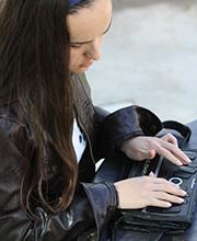 Arcos sitting on ledge reading BrailleNote Apex
